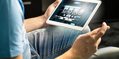 Excited man playing in an online casino with tablet fingers crossed wishing and hoping to win