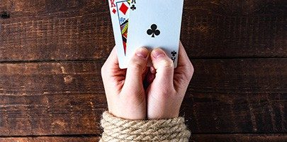 A person with tied hands holding playing cards