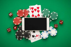 online casino concept, playing cards, dice chips and smartphone with copyspace on the green table.