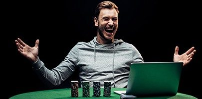 selective focus of happy man gesturing near poker chips near laptop isolated on black